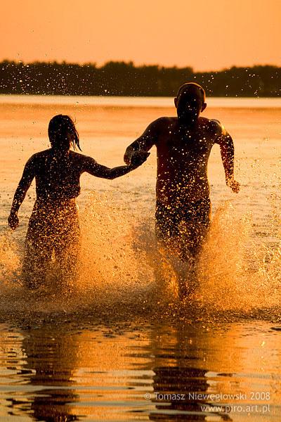 Zachód, para biegnie po jeziorze na Mazurach
