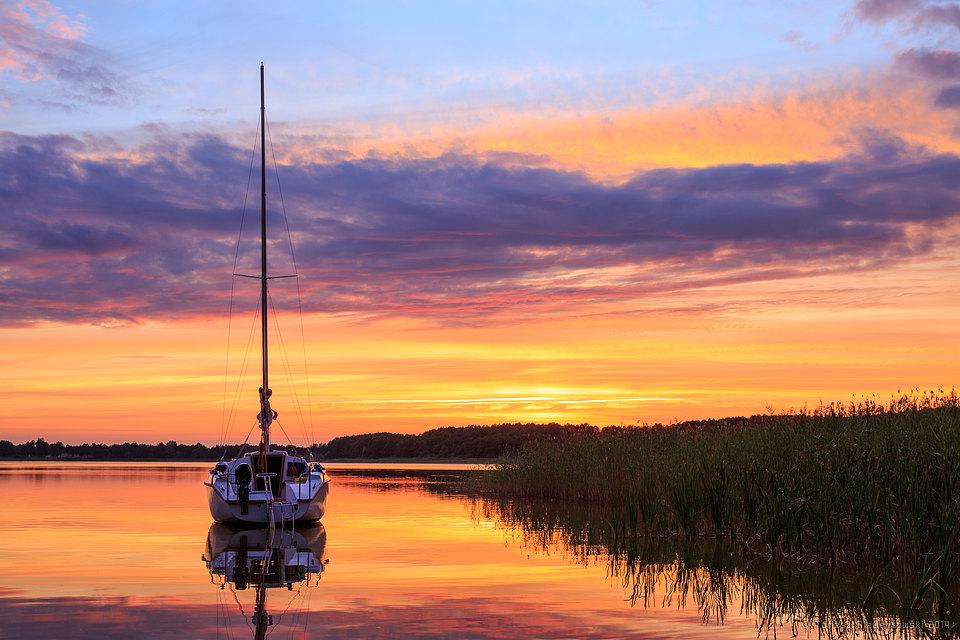 Żaglówka na jeziorze na Mazurach o zachodzie słońca
